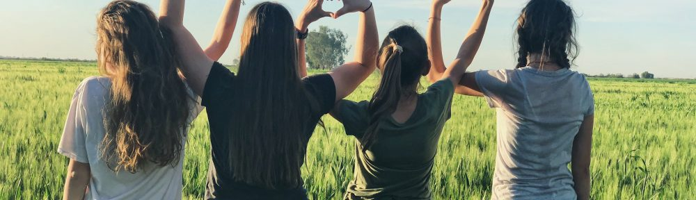 4 girls with backs turned towards camera making heart shapes with their arms